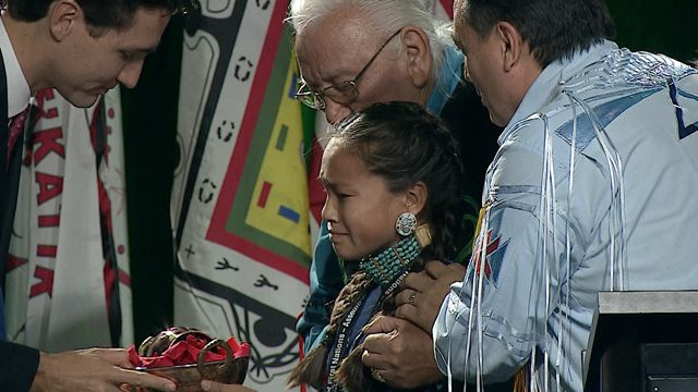 Autumn Peltier, 12, hands water bundle to Prime Minister Justin Trudeau. Autumn is flanked by AFN National Chief Perry Bellegarde and AFN Elder Elmer Courchene
