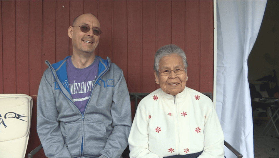 Strang Burton, a linguist, and Phillips sit outside of the elders home.